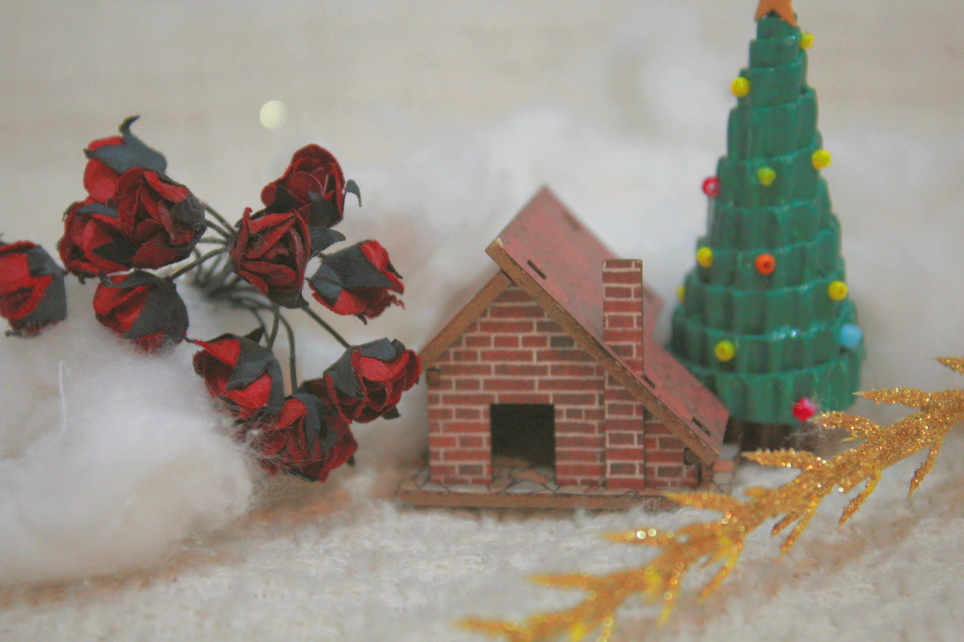 a small minatory house with red flowers and Christmas tree. snows around it.